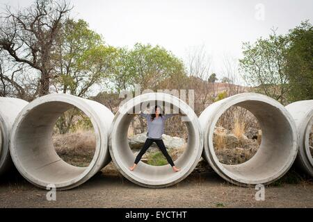 Portrait of young woman standing inside concrete pipe in rural landscape - Stock Photo