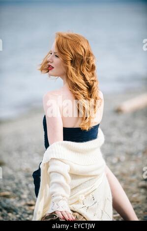 Young woman with long red hair looking over her shoulder on beach, Bainbridge Island, Washington State, USA - Stock Photo