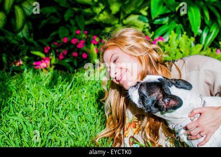 Dog licking woman's face in garden - Stock Photo