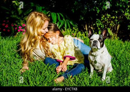 Mature woman, daughter and dog sitting in garden grass - Stock Photo