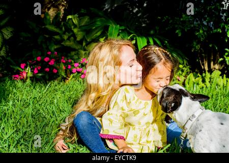 Dog licking girl's face in garden - Stock Photo