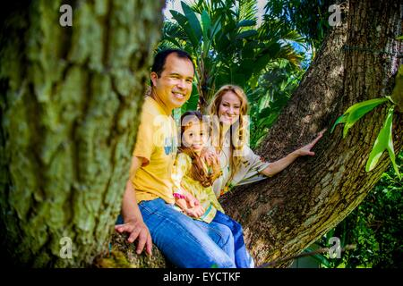 Portrait of mature couple and daughter sitting on garden tree branch - Stock Photo