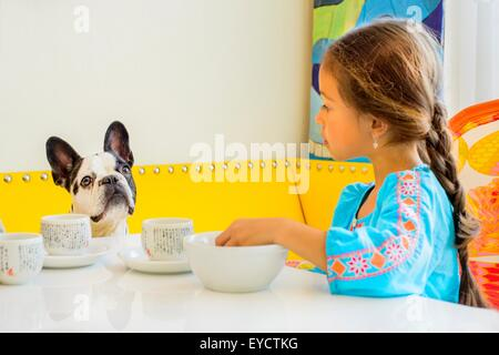 Girl and dog looking at each other at table - Stock Photo