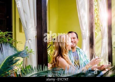 Mature couple sitting drinking white wine  in garden porch - Stock Photo