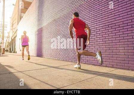 Rear view of male and female runners running along sidewalk - Stock Photo