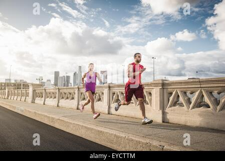 Male and female runners running across bridge, Los Angeles, California, USA - Stock Photo