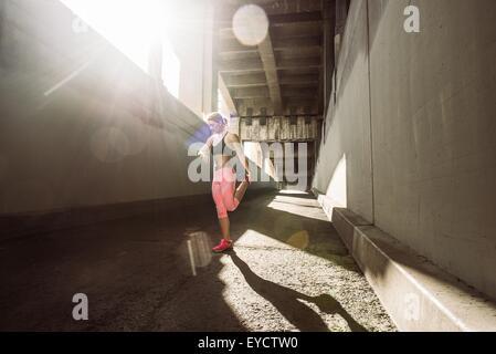 Female runner warming up under city bridge - Stock Photo