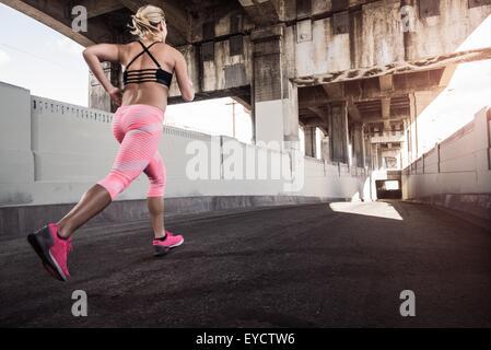 Female runner running under city bridge - Stock Photo