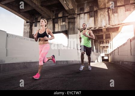 Female and male runners running under city bridge - Stock Photo