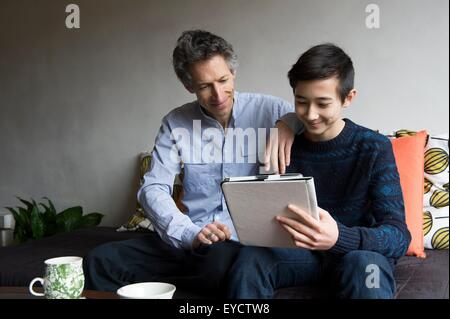 Father and teenage son reading digital tablet on sofa - Stock Photo