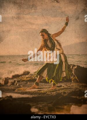 Enhanced image of woman hula dancing on coastal rocks wearing traditional costume, Maui, Hawaii, USA - Stock Photo