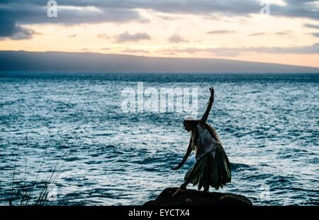 Silhouetted woman hula dancing on coastal rocks wearing traditional costume at dusk, Maui, Hawaii, USA - Stock Photo