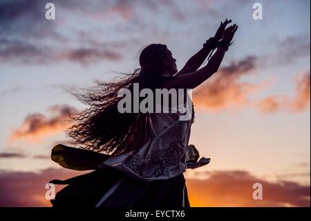 Silhouetted woman hula dancing wearing traditional costume at dusk, Maui, Hawaii, USA - Stock Photo