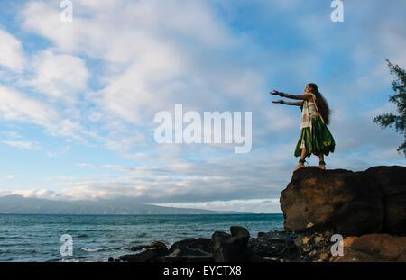 Woman hula dancing on top of coastal rocks wearing traditional costume, Maui, Hawaii, USA - Stock Photo
