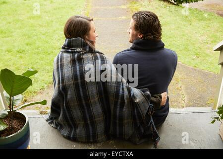 Rear view of young couple sitting on porch step - Stock Photo