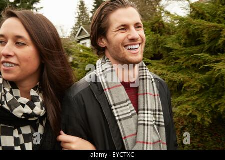 Young couple strolling arm in arm in park - Stock Photo