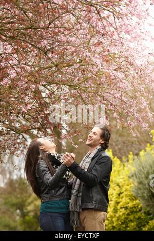 Young couple dancing under blossom in park - Stock Photo
