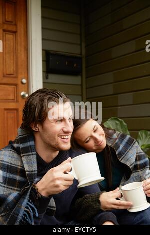 Young couple sitting on porch step wrapped in blanket - Stock Photo