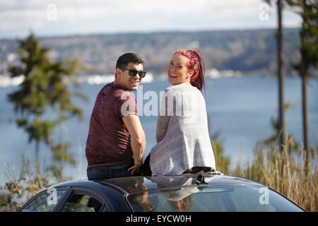 Portrait of young couple sitting on car roof at lakeside looking back - Stock Photo