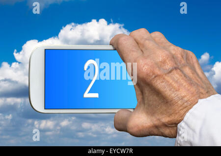 Smart phone in old hand with number TWO on screen. Selective focus - Stock Photo