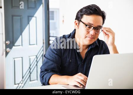 Mature businessman concentrating on laptop in kitchen - Stock Photo