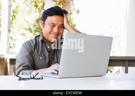 Frustrated mature businessman working on laptop in porch - Stock Photo
