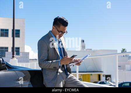 Young businessman in city car park reading smartphone texts - Stock Photo