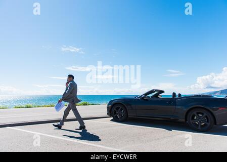 Young businessman at parking lot by the ocean, walking and talking on cellphone - Stock Photo