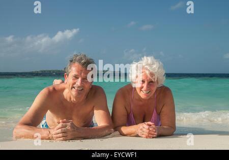 Senior couple lying on beach, Maldives - Stock Photo