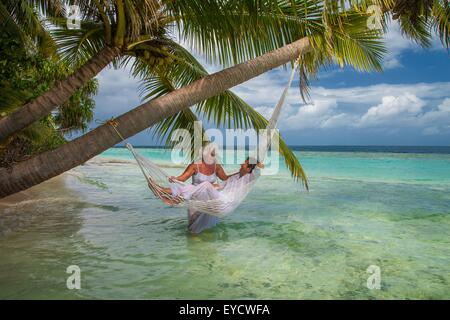 Senior man relaxing in hammock with woman, Maldives - Stock Photo