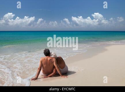Senior couple sitting on beach, Maldives - Stock Photo