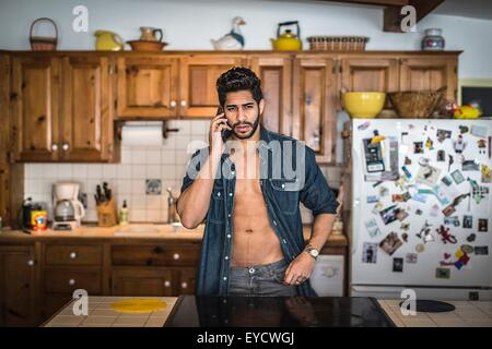 Young man on cell phone in kitchen - Stock Photo