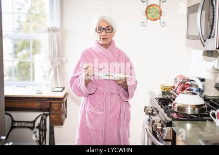 Senior woman standing in kitchen holding plate of food - Stock Photo