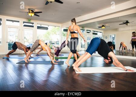 Yoga instructor in class with people in downward dog position - Stock Photo