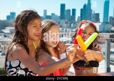 Girls eating ice lollies - Stock Photo