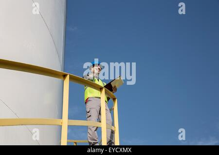 Male worker standing on steps of storage container at fuel depot, low angle view - Stock Photo