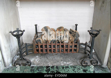 A Vintage Fireplace with Wooden Logs in the Grate. - Stock Photo