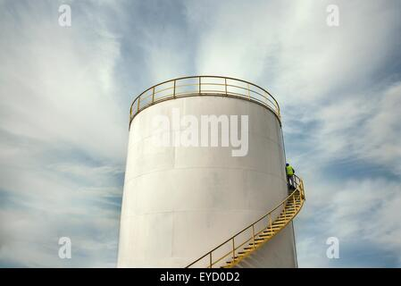 Industrial worker climbing stairs on oil storage tank - Stock Photo