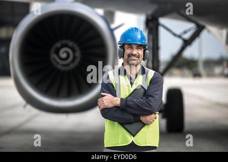 Portrait of male worker in front of airplane at Larnaca airport, Cyprus - Stock Photo