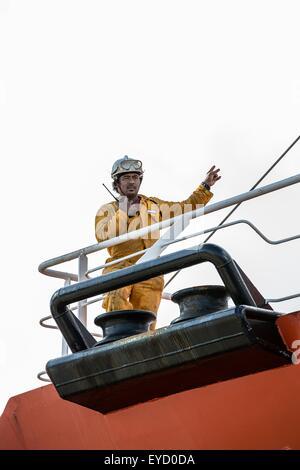Worker using walkie talkie on oil tanker deck - Stock Photo
