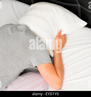 closeup of a young man face down in bed covering tightly his head with a pillow - Stock Photo