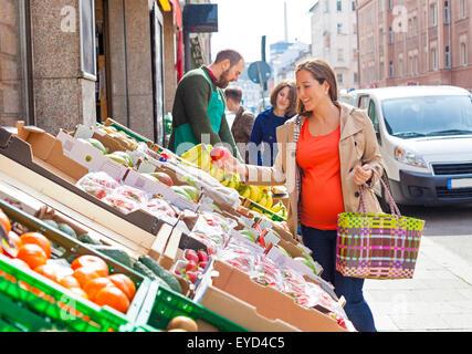 Woman choosing fruit in greengrocer's shop - Stock Photo