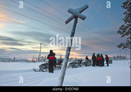 A Group Of People With Snowmobiles Enjoying The View Near Levi, Lapland, Finland - Stock Photo