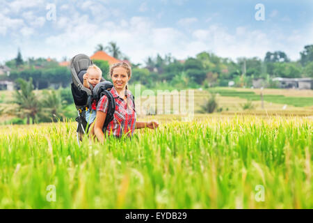 Nature walk in green rice terrace fields. Mother hold little traveler in backpack carrier. Travel adventure, trekking - Stock Photo