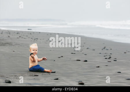 Portrait of smiling child sitting and playing alone with fun on balinese black sand sea beach before swimming. Family - Stock Photo