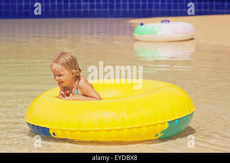 Funny portrait of cheerful baby girl swimming with fun on yellow tube in aqua park pool. Healthy family and children - Stock Photo