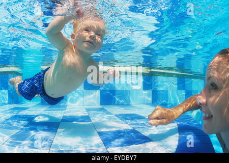 Portrait of child swimming with fun underwater in pool with diving cheerful mother. - Stock Photo