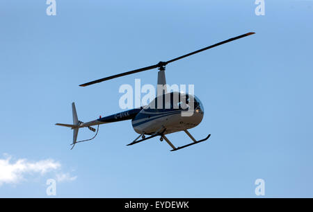 An R44 Helicopter pleasure flight,  taking pace over the race track, during the Silverstone Classic. - Stock Photo