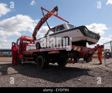 A 1965 Ford Lotus Cortina Mk1 with a collapsed rear suspension being recovered onto a flatbed truck, at the Silverstone - Stock Photo