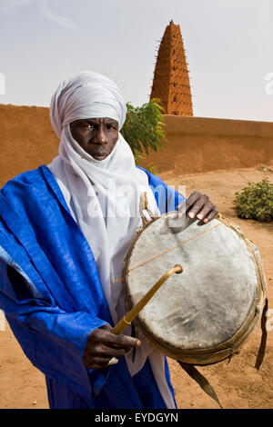 Niger, Sahara Desert, Agadez Region, Tuareg drummer standing next to Agadez Grand Mosque; Agadez - Stock Photo